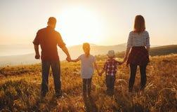 Lycklig familj: moder, fader, barn son och dotter p? solnedg?ng royaltyfri foto