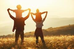 Lycklig familj: moder, fader, barn son och dotter p? solnedg?ng arkivfoto