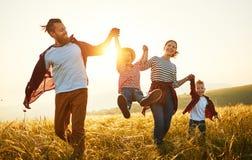 Lycklig familj: moder, fader, barn son och dotter p? solnedg?ng fotografering för bildbyråer