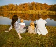 Lycklig familj - moder, fader och döttrar som kopplar av på höst c Arkivfoto