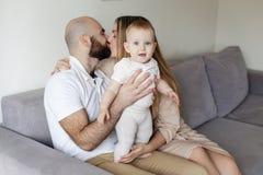 Lycklig familj, moder och fader som lite spelar med dottern hemma kopiera avstånd Kyssa familjpar och att behandla som ett barn f royaltyfri foto