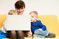 Lycklig familj. Moder och söner som hemma använder bärbar datorsammanträde på soffan Arkivfoto