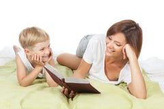 Lycklig familj - moder och son som ligger på den vita sängen arkivfoton