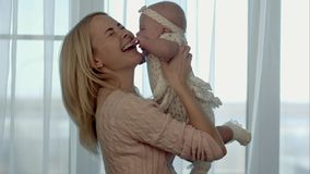 lycklig familj Modern kastar upp, och kyssa behandla som ett barn royaltyfri bild
