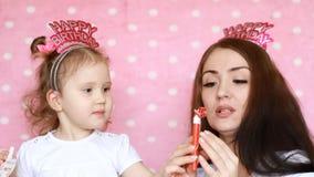 Lycklig familj - modern och dottern firar födelsedagen och blåsahorn Begreppet av en ferie, parti, födelsedag stock video
