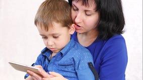 Lycklig familj: modern och sonen rymmer en smartphone i deras händer och trycker på pekskärmen Kvinna- och barnlek stock video