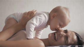 lycklig familj modern som spelar med henne, behandla som ett barn i sovrummet skratta le lager videofilmer