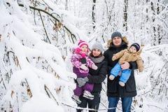 Lycklig familj mot bakgrunden av snö-täckte träd royaltyfria bilder