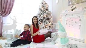 Lycklig familj och julgåvor på julafton lager videofilmer