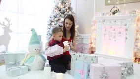 Lycklig familj och många julgåvor på julgranen i ett festligt rum lager videofilmer