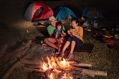 Lycklig familj på att campa med lägereld royaltyfria foton