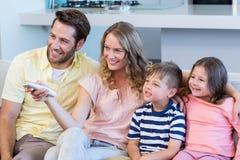 Lycklig familj på den hållande ögonen på tv:n för soffa Arkivbild