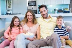 Lycklig familj på den hållande ögonen på tv:n för soffa Royaltyfri Fotografi