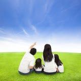 Lycklig familj på en äng med molnbakgrund royaltyfri fotografi