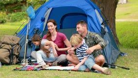 Lycklig familj på en campa tur framme av deras tält lager videofilmer