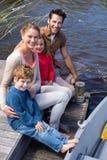 Lycklig familj på en sjö arkivfoto