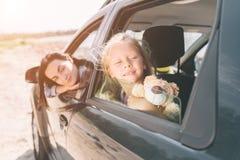 Lycklig familj på en vägtur i deras bil Farsan, mamman och dottern reser vid havet eller havet eller floden arkivbild