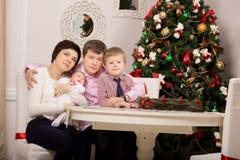 Lycklig familj på ferietabellen Träd Jul arkivfoto