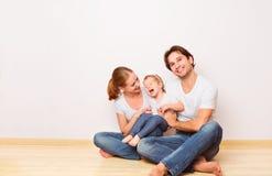 Lycklig familj på golv nära den tomma väggen i den köpta lägenheten Royaltyfri Fotografi