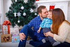 Lycklig familj på jul i huset på bakgrunden av en julgran som kysser deras son arkivfoto