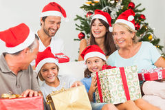 Lycklig familj på jul som byter gåvor Arkivbilder