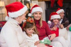 Lycklig familj på jul som rymmer gåvor Arkivbilder