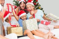 Lycklig familj på jul som tillsammans öppnar gåvor Arkivfoto