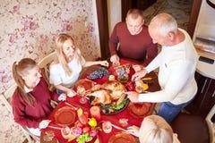 Lycklig familj på matställetabellen som firar tacksägelse på en suddig bakgrund Traditionellt tacksägelsebegrepp Royaltyfria Bilder