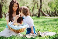 Lycklig familj på picknicken för moderdag Mamma- och litet barnson som äter sötsaker som är utomhus- i vår royaltyfri fotografi