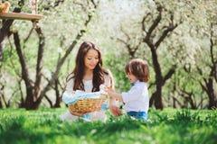 Lycklig familj på picknicken för moderdag Mamma- och litet barnson som äter sötsaker som är utomhus- i vår arkivbilder