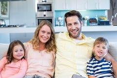 Lycklig familj på soffan arkivbilder