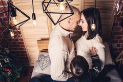 Lycklig familj på soffan i jultid i förväntan av miraklet royaltyfri foto