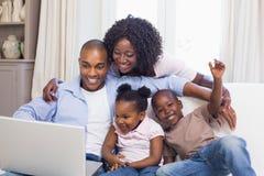 Lycklig familj på soffan som använder tillsammans bärbara datorn royaltyfri foto