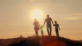 Lycklig familj på solnedgångsilhouette Arkivfoton