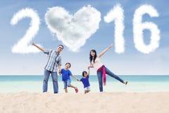 Lycklig familj på stranden med nummer 2016 Arkivbild