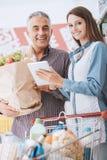 Lycklig familj på supermarketen arkivbild