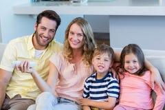 Lycklig familj på den hållande ögonen på tv:n för soffa Royaltyfri Bild