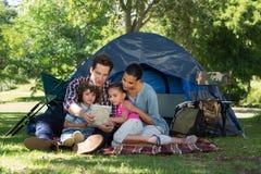 Lycklig familj på en campa tur i deras tält Arkivfoton