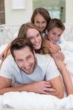 Lycklig familj på sängen Arkivfoto