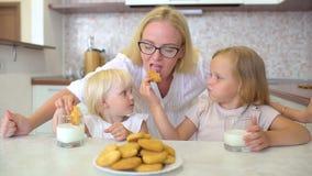 lycklig familj Små flickor med blont hår som har, mjölkar och kakor med deras moder som är hemmastadd i köket Childs stock video