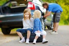 Lycklig familj som ändrar ett bilhjul Royaltyfria Bilder