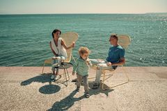 Lycklig familj som äter glass Den gulliga sonen tycker om sommarsemester Föräldrar med barnet äter glass på kusten bakgrundschokl Arkivfoto