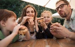 Lycklig familj som äter hamburgare som sitter på en tabell i ett kafé royaltyfria foton