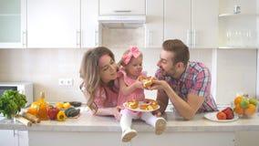 Lycklig familj som äter kakan i köket Arkivfoto