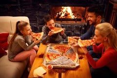 Lycklig familj som äter pizzaskivor för matställen royaltyfri foto