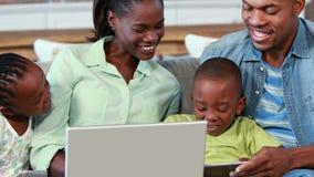 Lycklig familj som använder en bärbar dator lager videofilmer