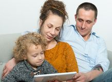 Lycklig familj som använder en minnestavla Royaltyfri Bild