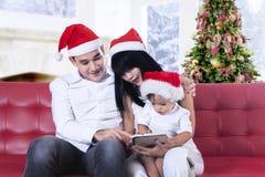 Lycklig familj som använder minnestavladatoren Fotografering för Bildbyråer