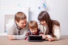 Lycklig familj som använder minnestavlan Arkivbild