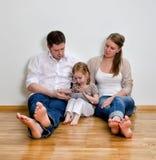 Lycklig familj som använder tabletdatoren Arkivbild